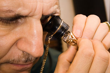 a gemologist examining a gemstone in a ring setting